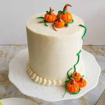 A frosted cake with cream cheese and fondant pumpkins.