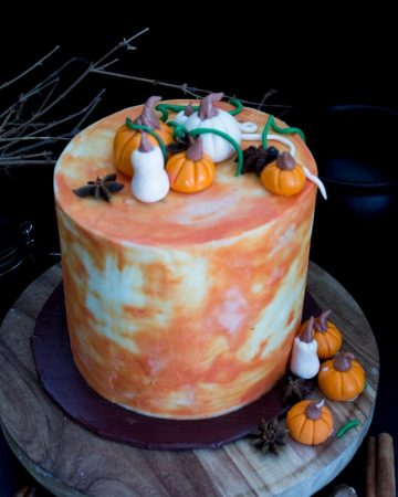 A frosted cake with fondant pumpkins on top