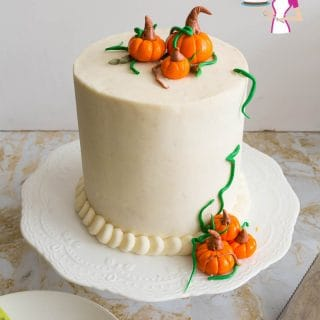 A pumpkin cake with frosting and pumpkin cake toppers.