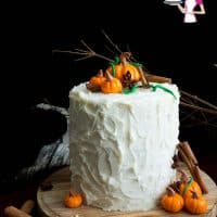 A pumpkin cake with buttercream frosting and pumpkin cake toppers.