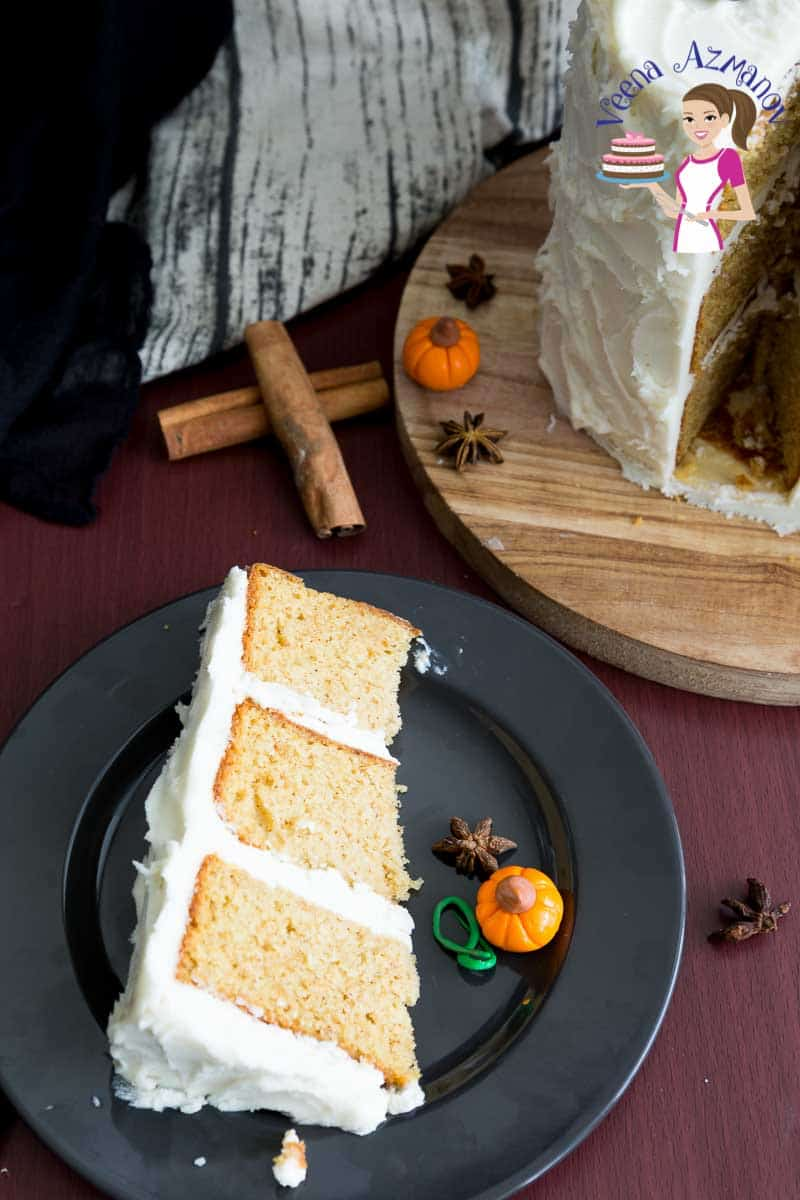 A slice of pumpkin cake with buttercream frosting on a plate.