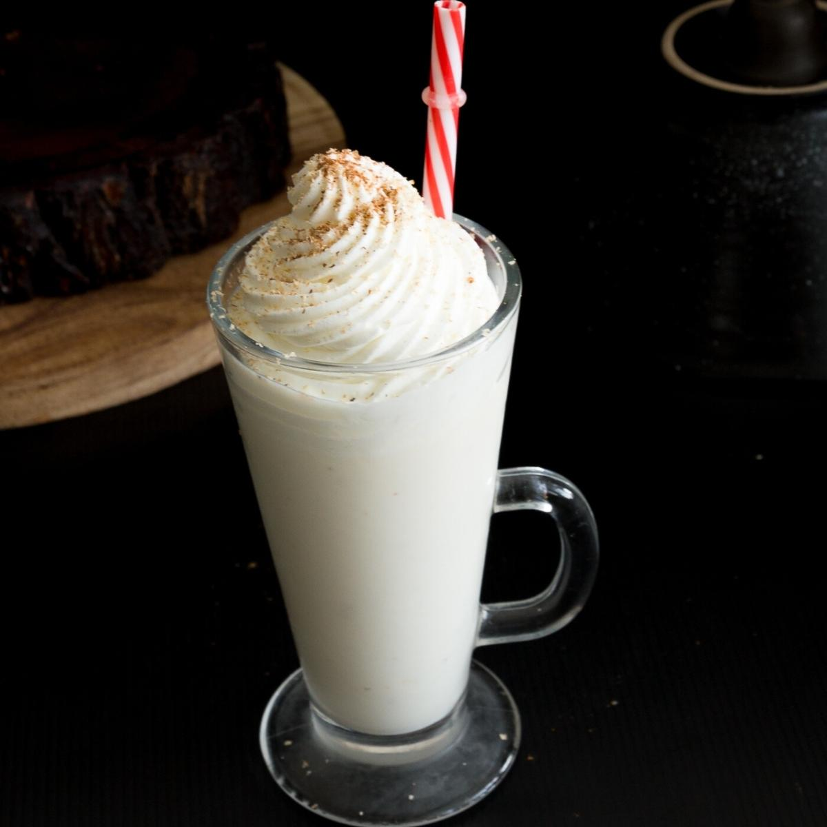 A tall glass of eggnog with whipped cream on top.