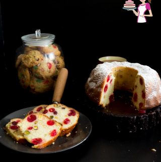 A slice of cherry bundt cake on a plate, next to the remaining cake on a stand.