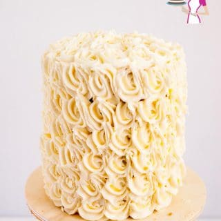 A frosted white wedding cake on a cake stand.