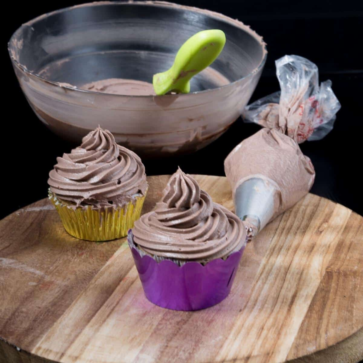 Frosted cupcakes on a wooden table.