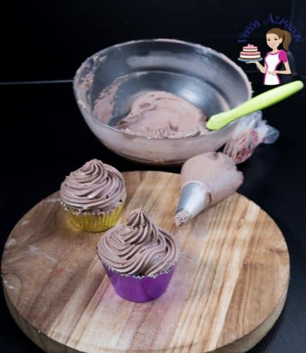 Two cupcakes with chocolate frosting on a round board.