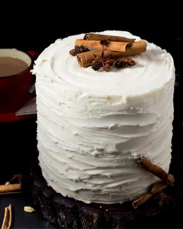 A layer cake with buttercream frosting and whole chai spices on top.
