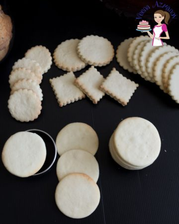 A stack of different shaped vanilla sugar cookies on a table.