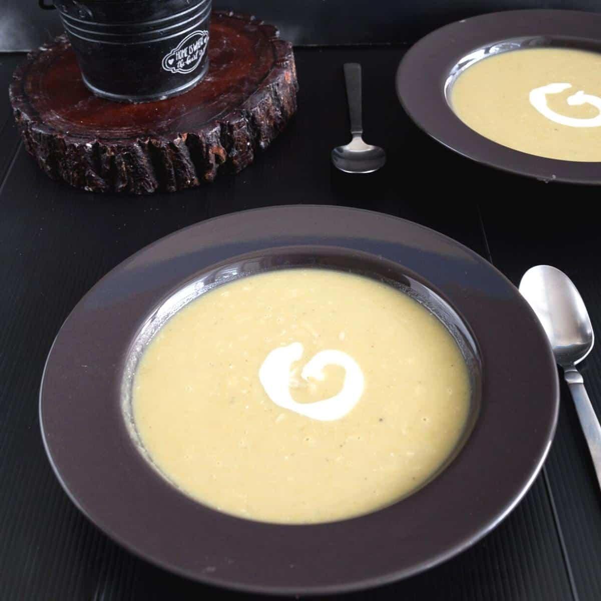 Two black soup bowls with split pea soup