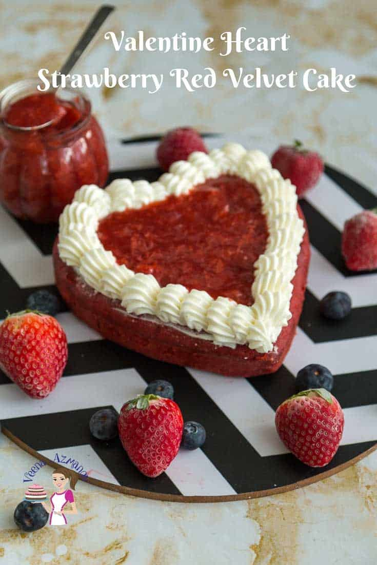 A red heart-shaped cake on a round board next to fresh strawberries.