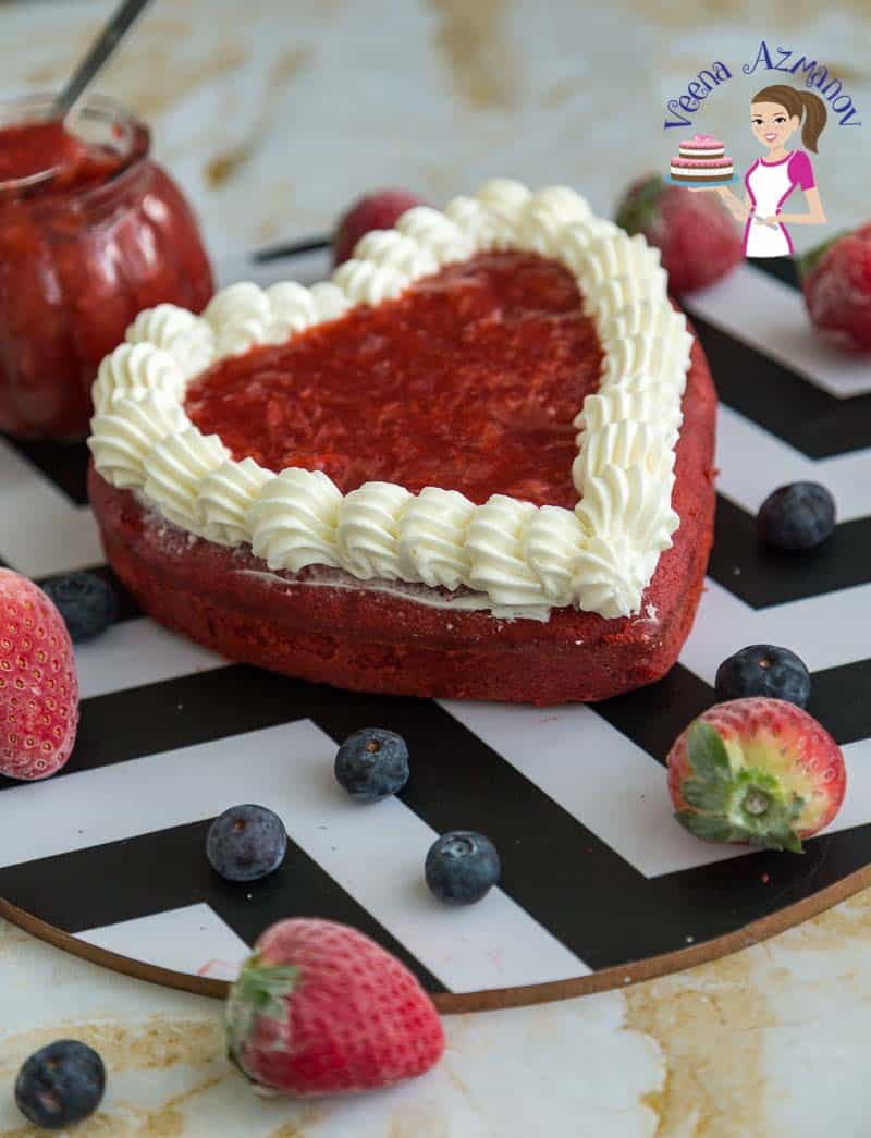 A red heart-shaped cake on a round board.