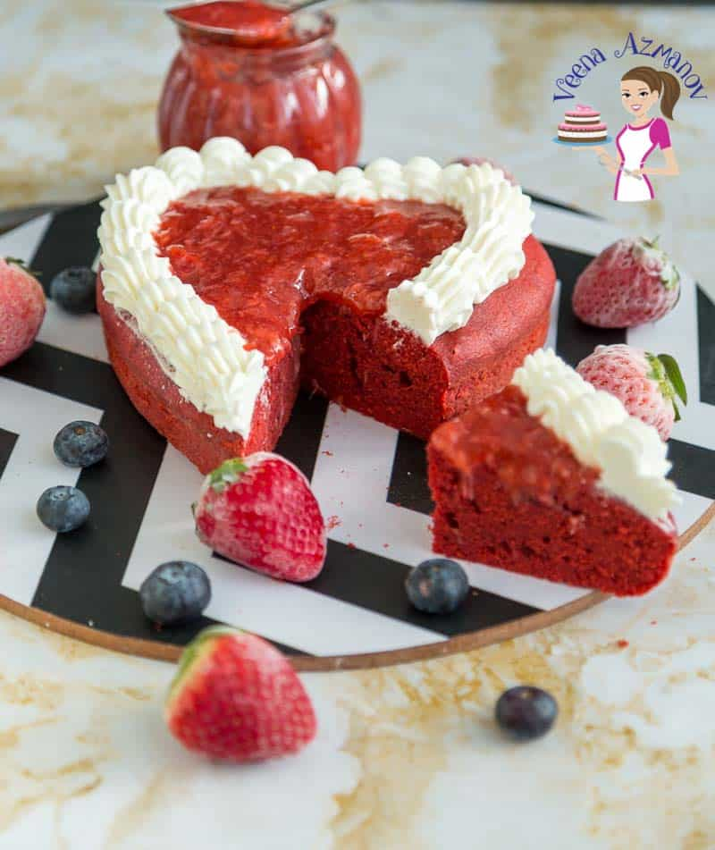 A sliced red heart-shaped cake on a round board next to fresh strawberries.