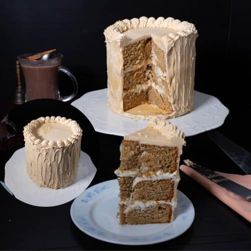 A plate with a slice of a layer cake with buttercream frosting.