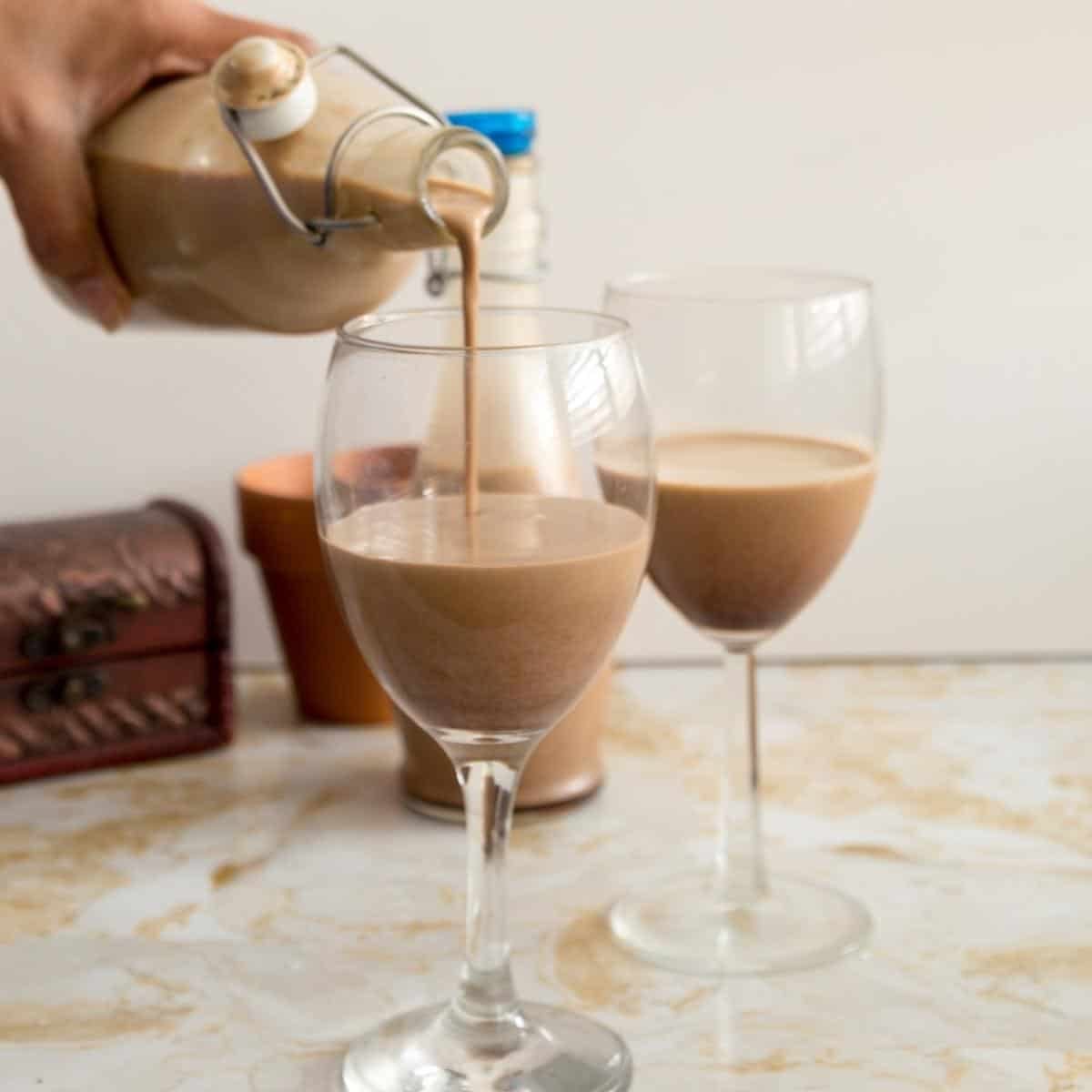 a bottle pouring baileys in a glass