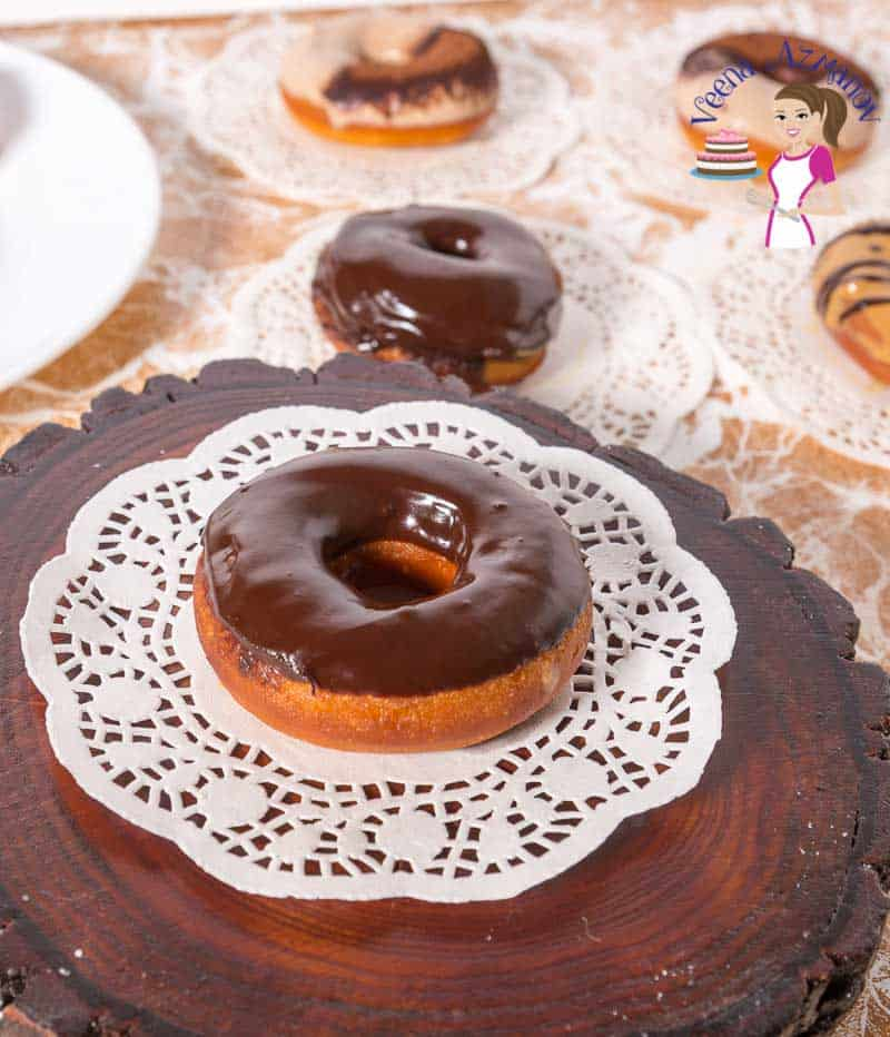 A display of chocolate glazed donuts on white doily with Tiramisu donuts, dulce de leche donuts in the background.