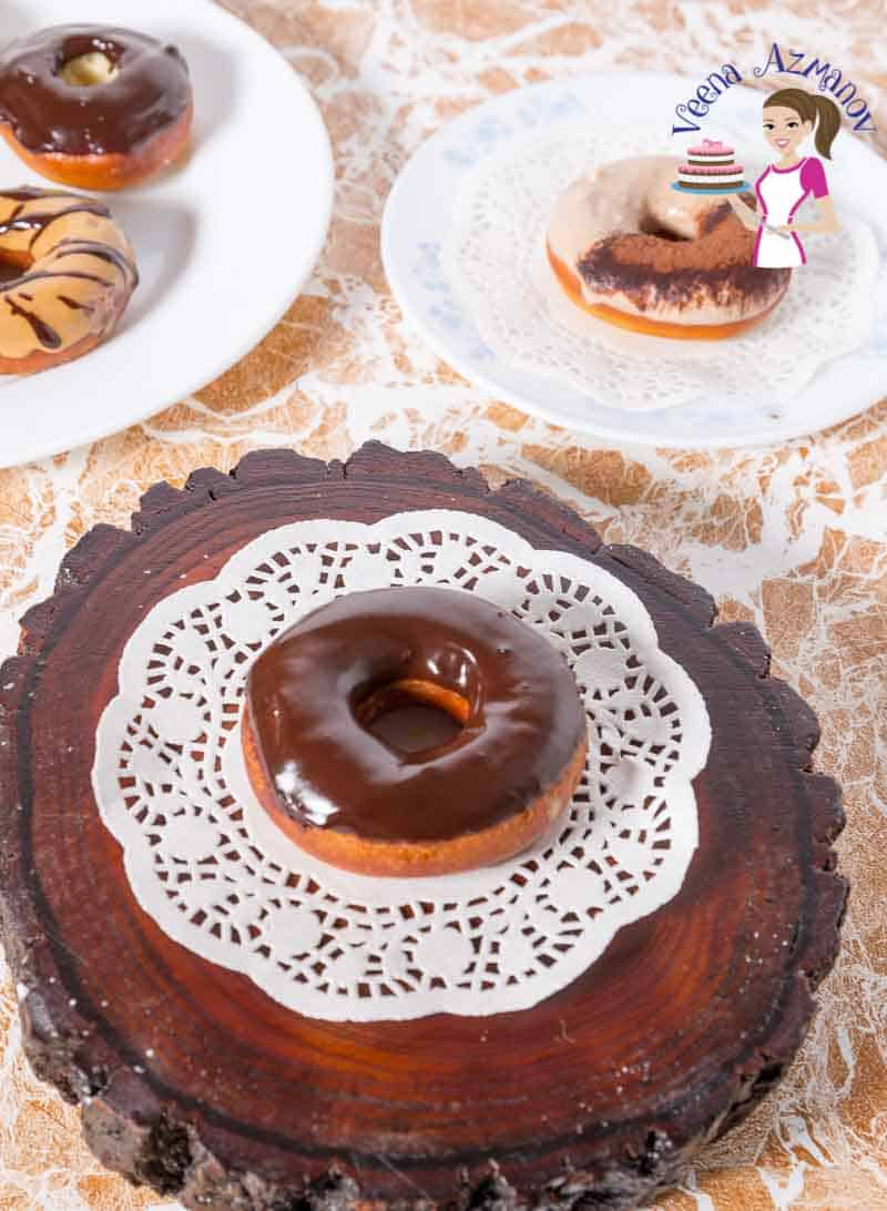 A display of chocolate glazed doughnuts on white doily with Tiramisu donuts, dulce de leche donuts in the background.