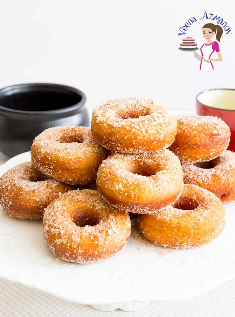 A stack of sugar donuts on a table.