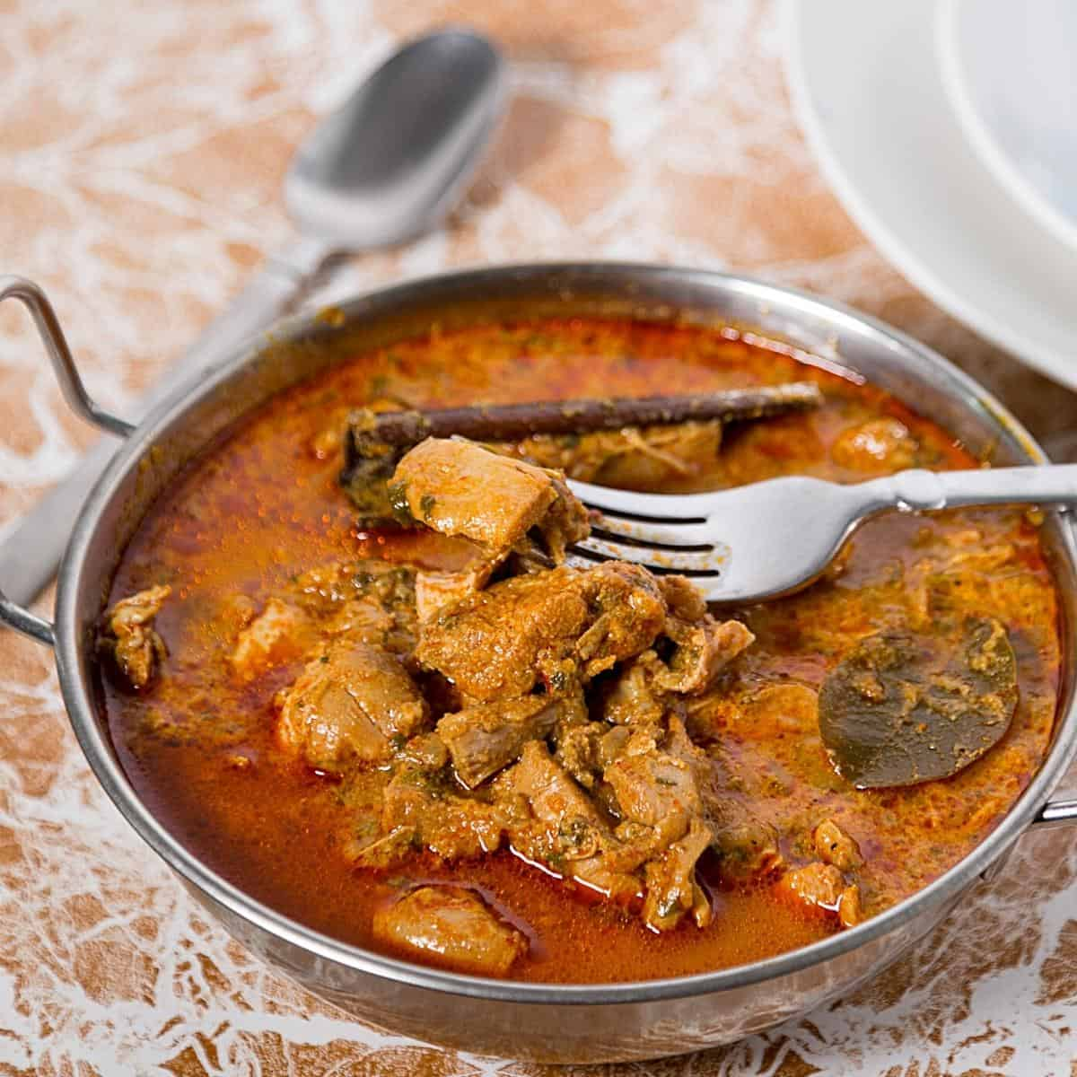 An Indian dish with chicken curry and fork.