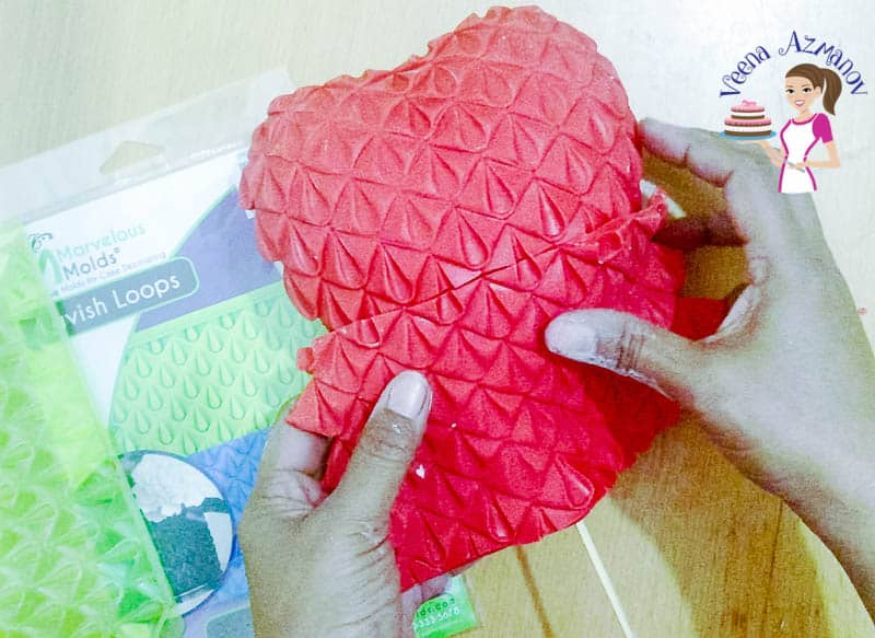 A person using a fondant  impression mat to cover a heart-shaped styrofoam.
