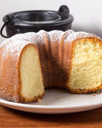 A cut vanilla bundt cake on a plate.