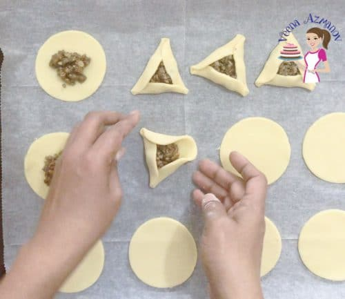 A person shaping cookie dough circles with pecan filling to make hamantaschen cookies.
