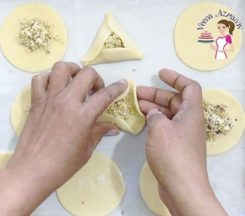 A person closing a hamantaschen cookie with halva and pistachio filling.