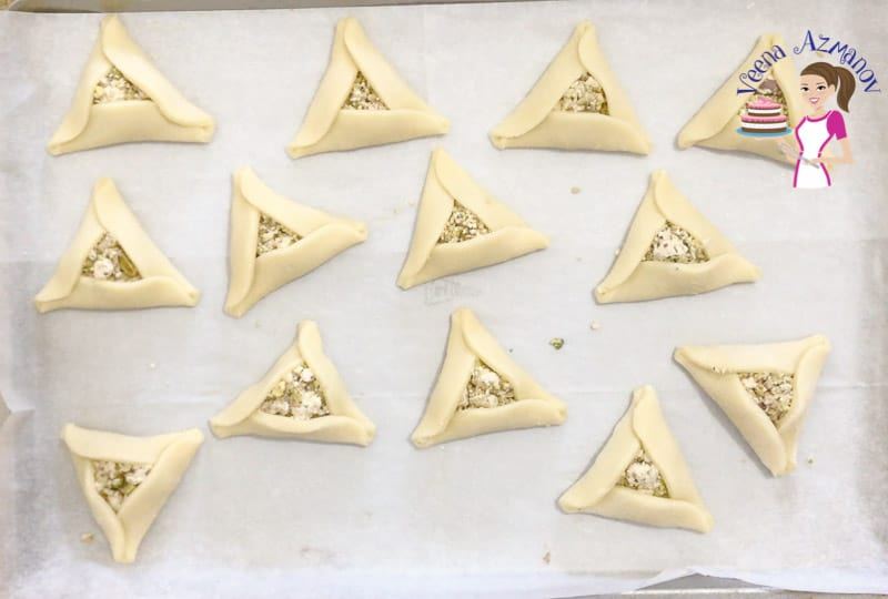 Unbaked hamantaschen cookies on a baking tray.