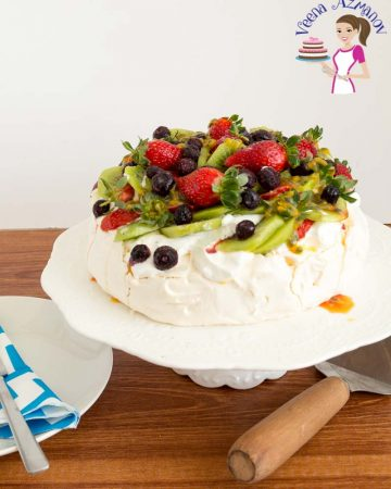 A pavlova with berries on top sitting on a cake stand.