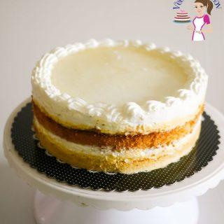 A mascarpone cream cake on a cake stand.