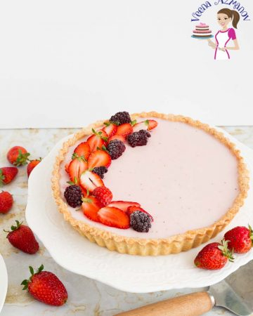 A strawberry Panna cotta tart on a cake stand.