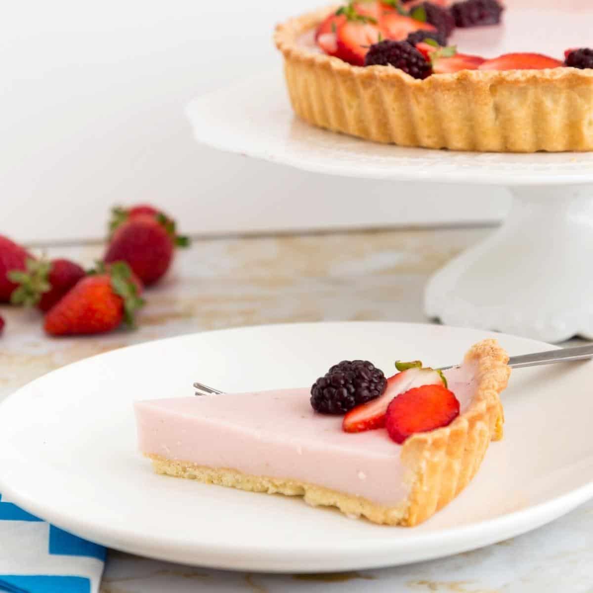 A slice tart on a cake stand