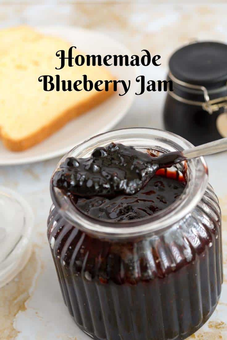 A close up of a jar of blueberry jam with a spoon full of jam.