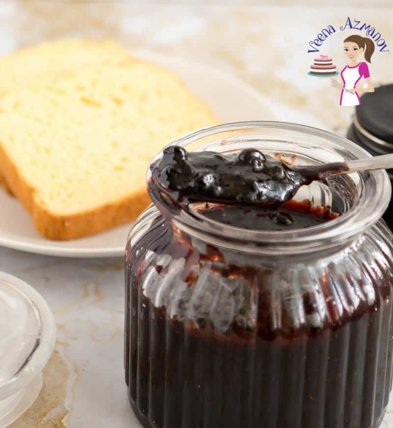 A jar of blueberry jam with a spoon full of jam.