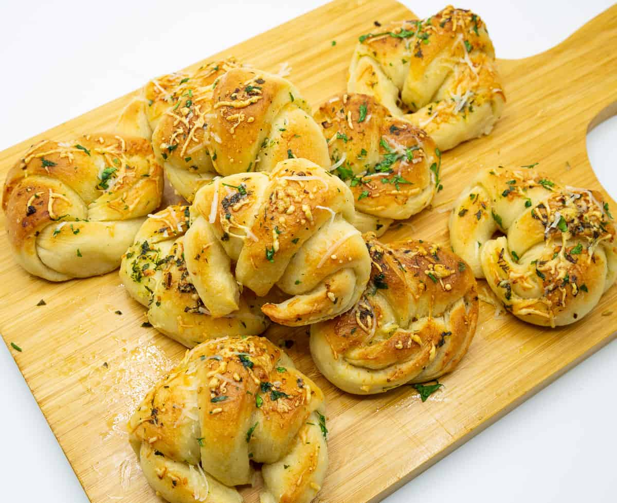 Wooden board with butter garlic rolls.
