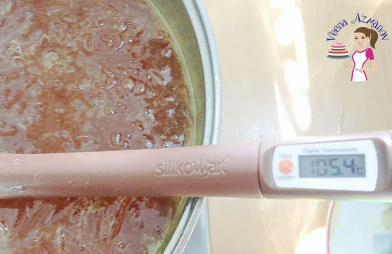 A close up of a thermometer in a pan of hot jam.