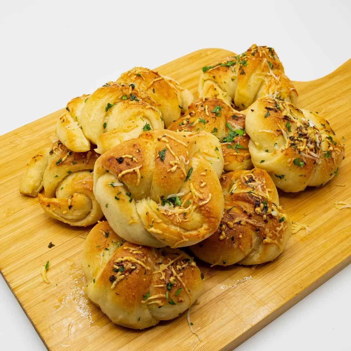 Garlic bread rolls on a wooden board.