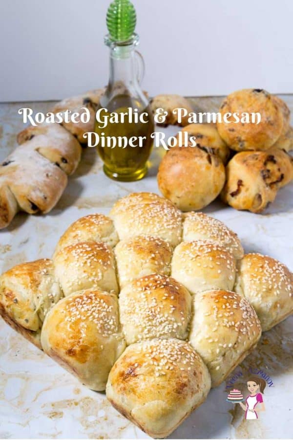 A stack of dinner rolls on a wooden board.