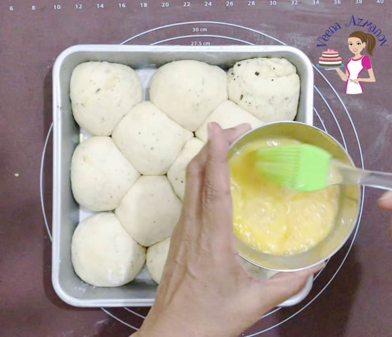 A person spreading egg wash on balls of dough for bread rolls in a square baking pan.