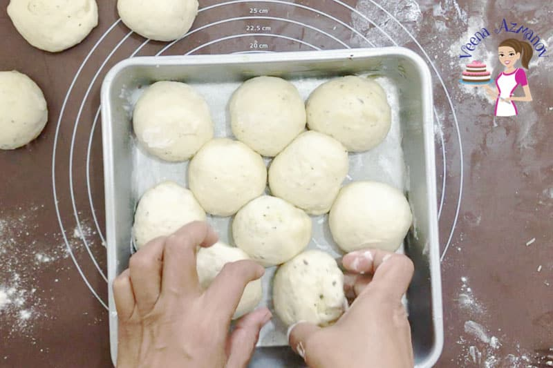 A person arranging balls of dough for bread rolls in a square baking pan.