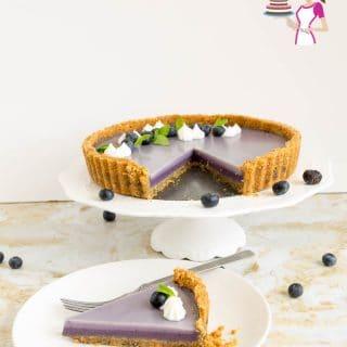 A slice of blueberry panna cotta tart on a plate.