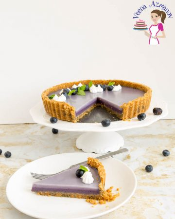 A slice of blueberry panna cotta tart on a plate.