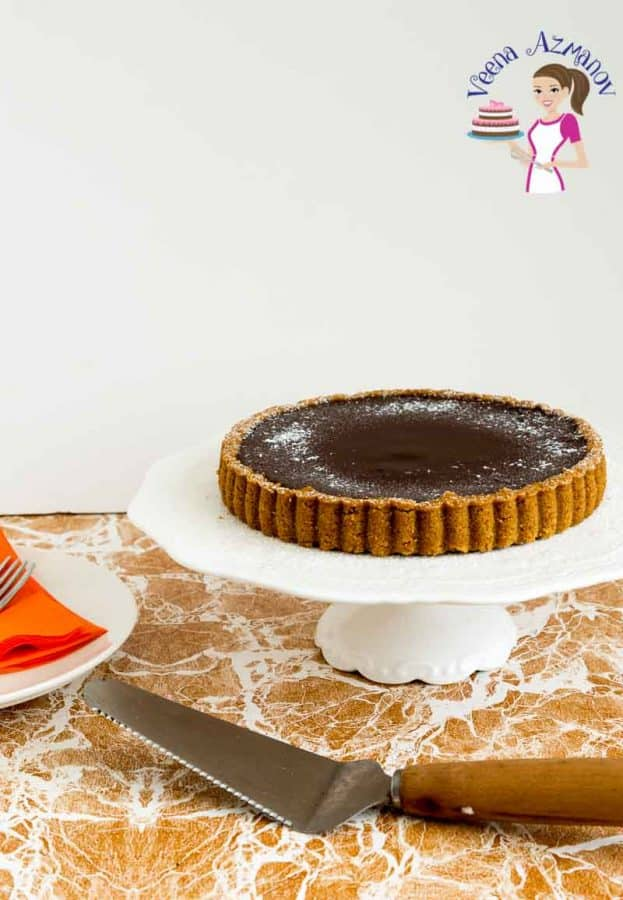 Chocolate cheesecake tart on a cake stand.