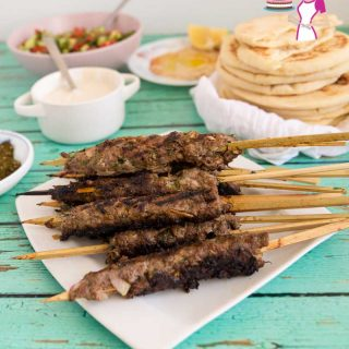 A stack of kebabs made with beef on a tray served with tahini, pita and hummus.