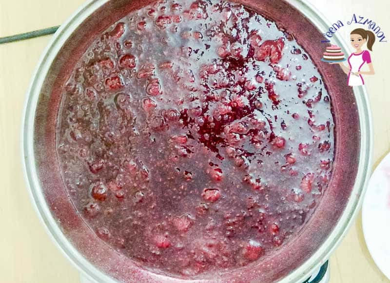 Simmering the raspberry jam on low for 20 minutes