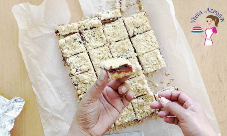 A person holding a piece of cherry crumble square.