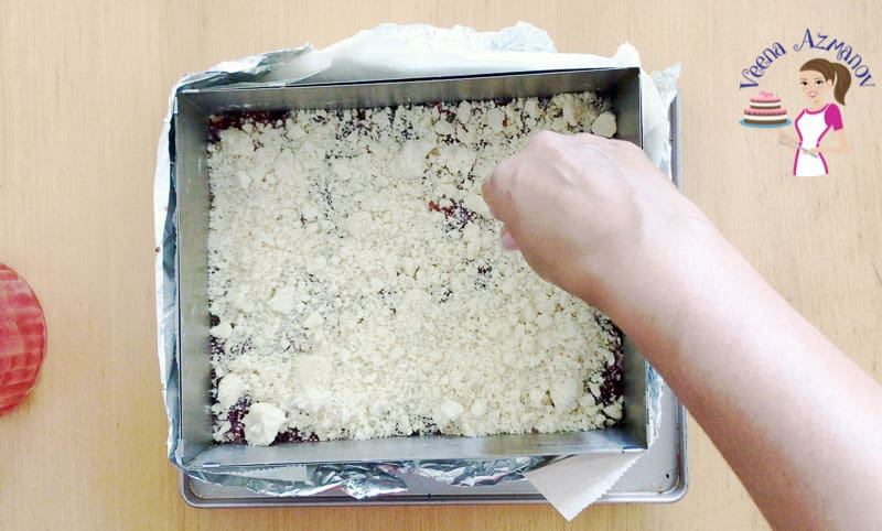 Progress photo of making a cherry crumble pie in a square pan.