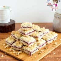Cherry pie crumble squares on a wooden board.