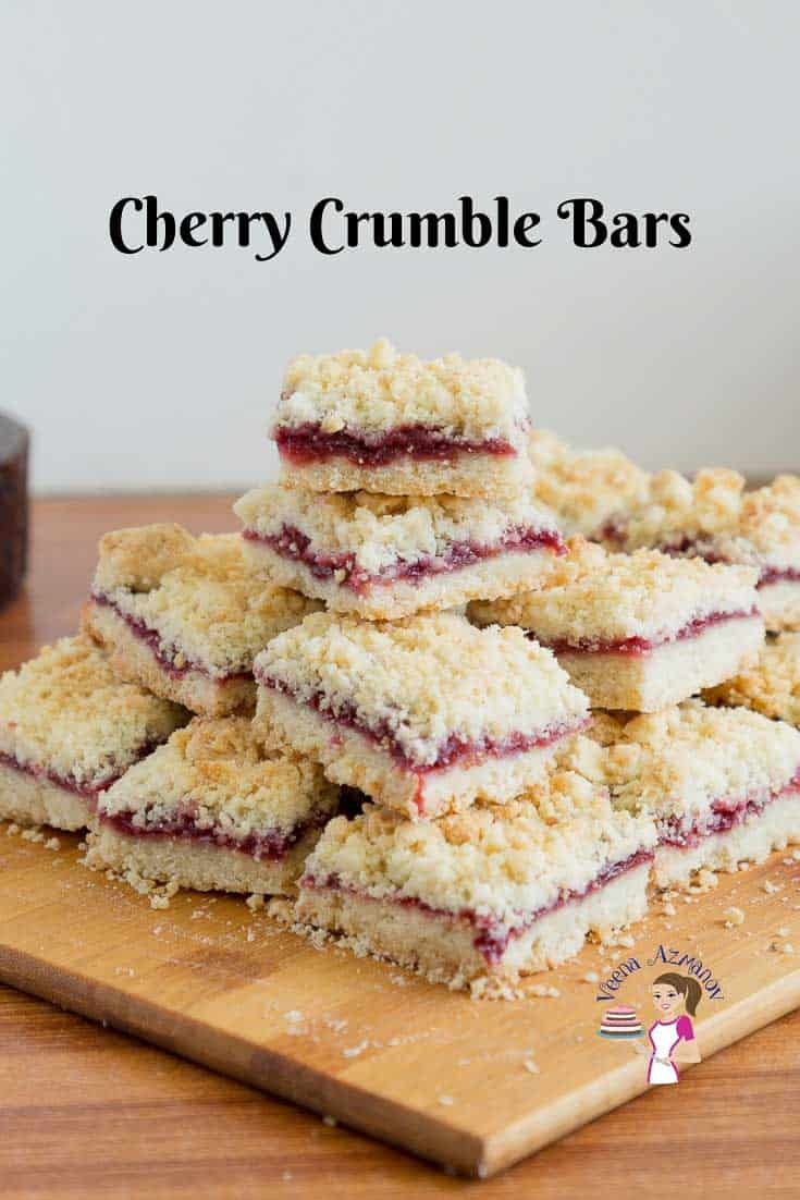 A stack of cherry crumble squares on a wooden board.