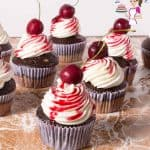 Chocolate cherry cupcakes on a table.
