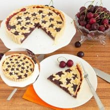 A pie with cherry filling on a cake stand.
